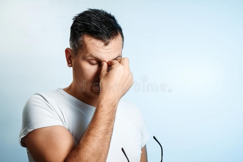 Close-up portrait of a man, covering his face with his hands. On a light background. The concept of body language stock image