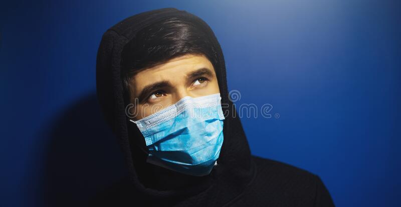 Close-up portrait of man looking up, wearing medical protective flu mask and hooded sweatshirt, on background of dark blue color. Close-up portrait of man stock photo