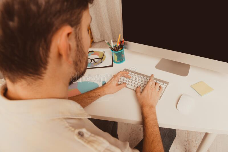 Close up portrait of man working on pc and typing stock photo