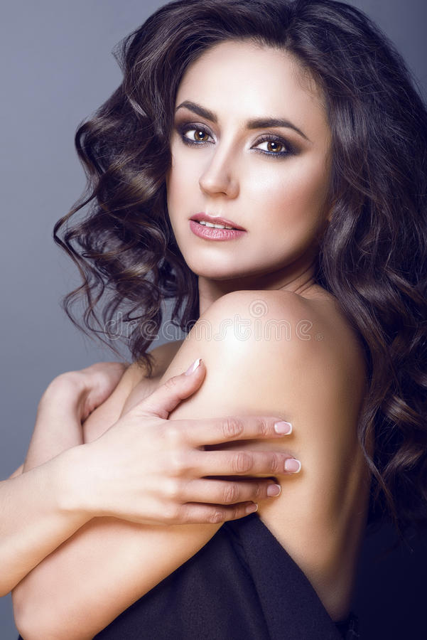 Close up portrait of middle aged beautiful brunette with perfect make-up and naked shoulders embracing herself stock image