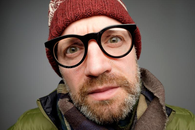 Close up portrait of middle aged europeam man in funny warm hat and glasses noticing hidden camera. Somebody is spying after me really stock photo