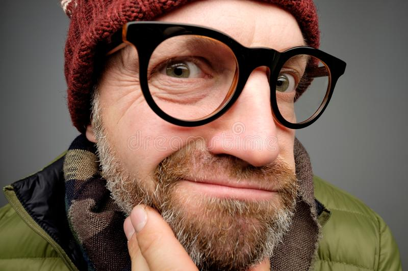 Close up portrait of middle aged europeam man in funny warm hat and glasses noticing hidden camera. Somebody is spying after me really stock images