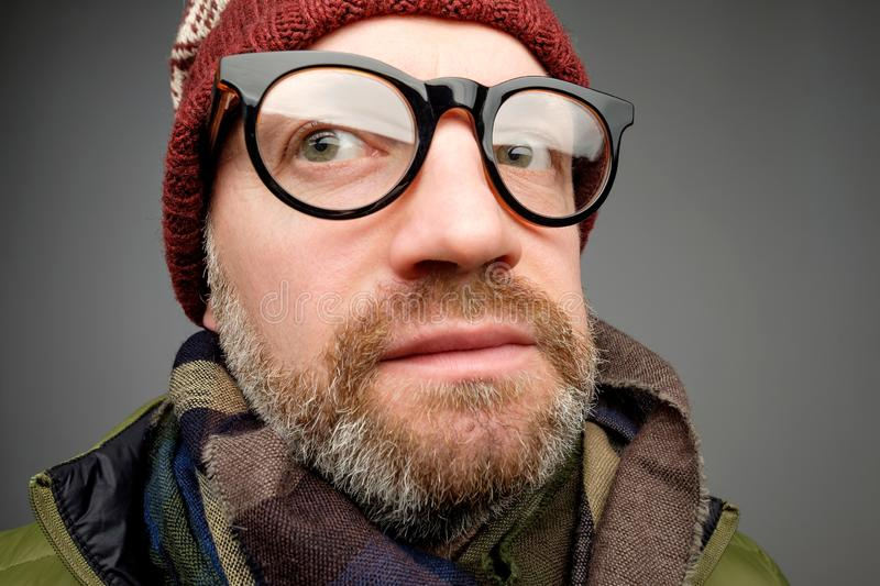 Close up portrait of middle aged europeam man in funny warm hat and glasses noticing hidden camera. Somebody is spying after me really stock photos