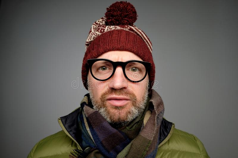 Close up portrait of middle aged europeam man in funny warm hat and glasses noticing hidden camera. Somebody is spying after me really royalty free stock photo