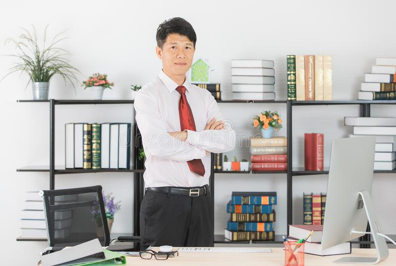 Asian business man at office. Close up portrait of middle aged, handsome, Asian, businessman, in white shirt, dark red necktie, black pants posing arms crossed royalty free stock photo