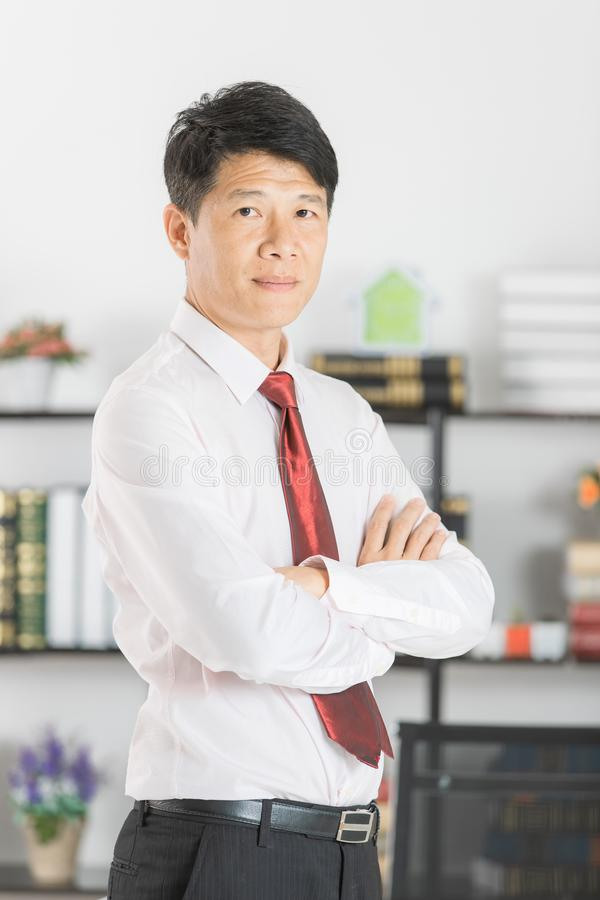 Asian business man at office. Close up portrait of middle aged, handsome, Asian, businessman, in white shirt, dark red necktie, black pants posing arms crossed stock image