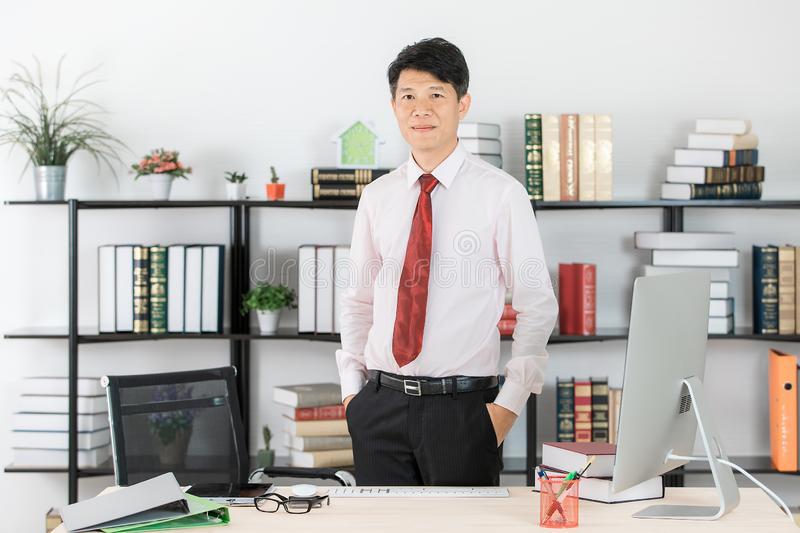 Asian business man at office. Close up portrait of middle aged, handsome, Asian, businessman, in white shirt, dark red necktie, black pants posing arms crossed stock photos