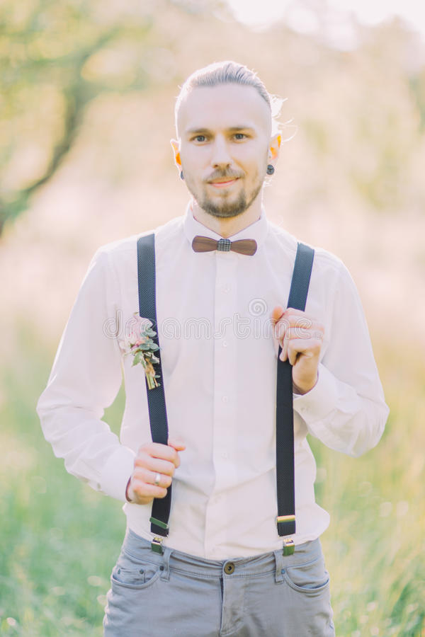 The close-up portrait of the modern-dressed groom in the gray pants, white shirt and wooden butterfly at the background stock photography