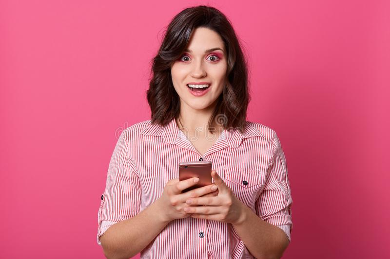 Close up portrait of modern women holding cellphone isolated over pink background, slim female dresses casual outfit, keeps mouth stock photos