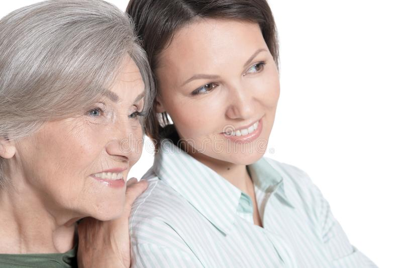 Close up portrait of mother and her adult daughter hugging isolated on white royalty free stock photo
