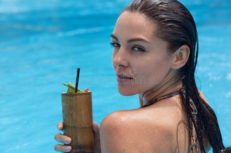 Close up portrait of mysterious attractive young woman swimming in swimming pool, spending her weekends at spa resort, looking stock image