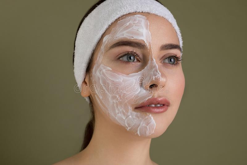 Close up portrait of naked young woman with blue eyes and red lips. With clay cosmetic mask at her face during procedures in a beauty salon  on grey background stock photo
