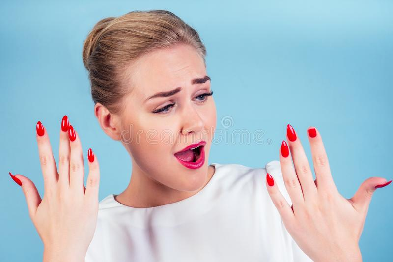 Close-up portrait of nervous unhappy young blonde woman looking at a broken fingernail and crying . red long nails royalty free stock photos