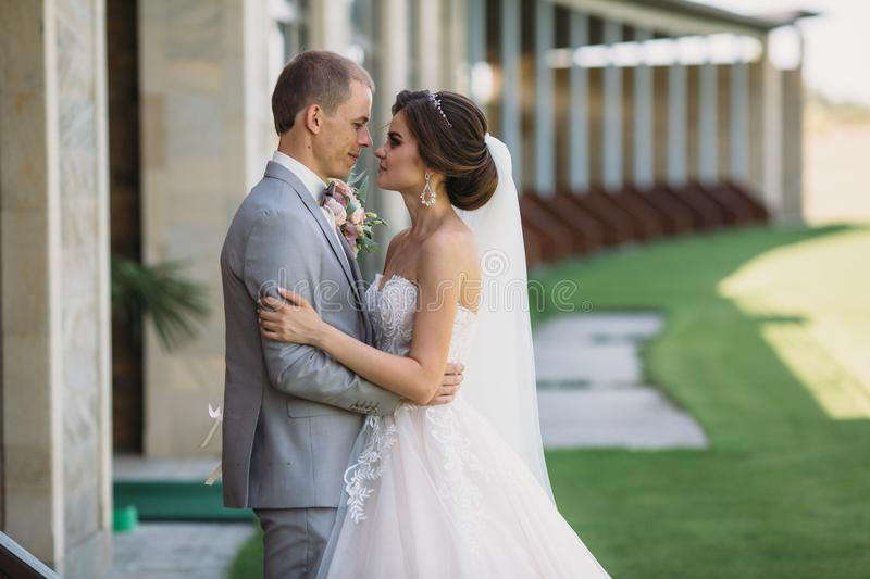Close-up portrait of newlyweds on wedding day. The bride hugs with the groom before the kiss. Man in business suit and. Girl in white dress with veil. Marriage royalty free stock images