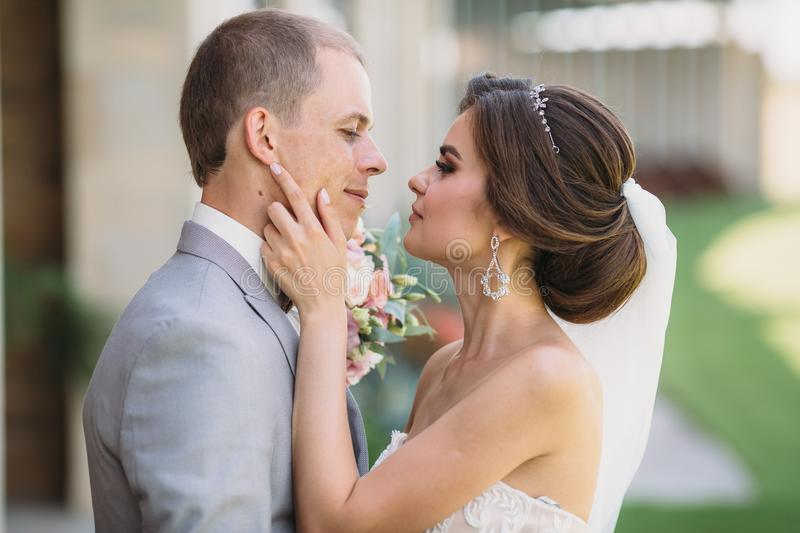 Close-up portrait of newlyweds on wedding day. The bride hugs with the groom before the kiss. Man in business suit and. Girl in white dress with veil. Marriage royalty free stock photos