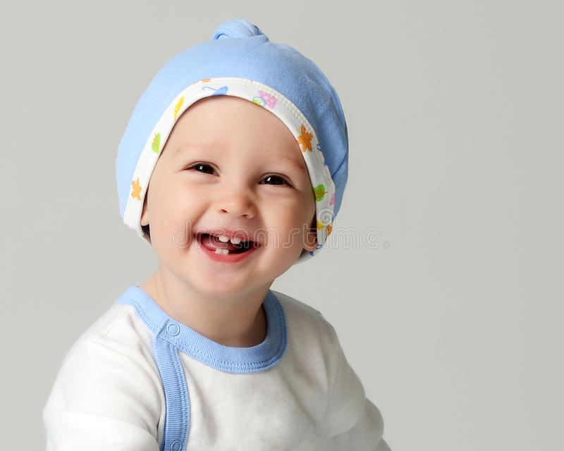 Close up portrait of nfant child baby boy kid toddler in light blue body cloth and hat. Looking at the corner on gray background royalty free stock images