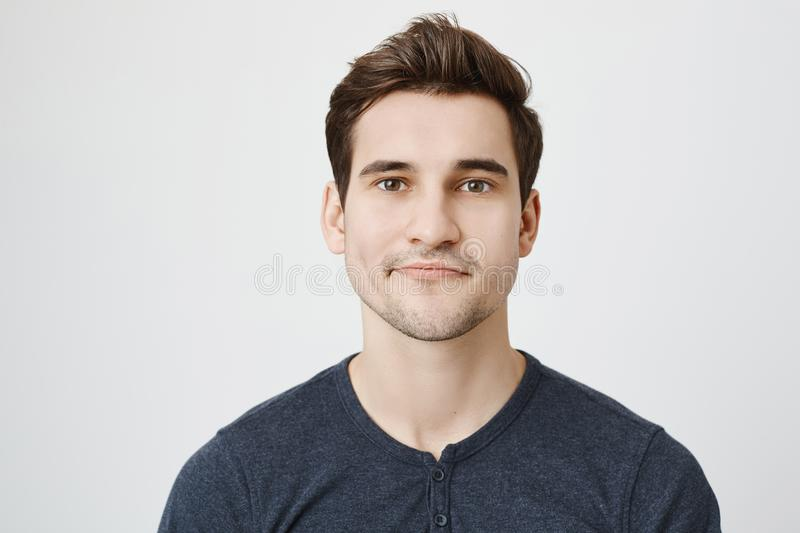 Close-up portrait of nice european guy with stylish haircut and curvy smile, standing against gray background. Student stock image
