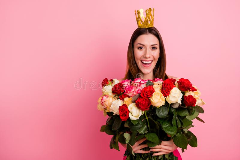 Close-up portrait of nice-looking attractive lovely cheerful cheery glad girl holding in hands big large bouquet. Different roses stem wearing, tiara  over pink royalty free stock photo