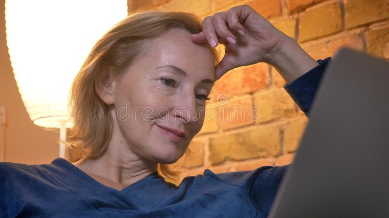 Close-up portrait of old caucasian woman working with laptop smilingly and leaning on hand in cozy home atmosphere. royalty free stock image