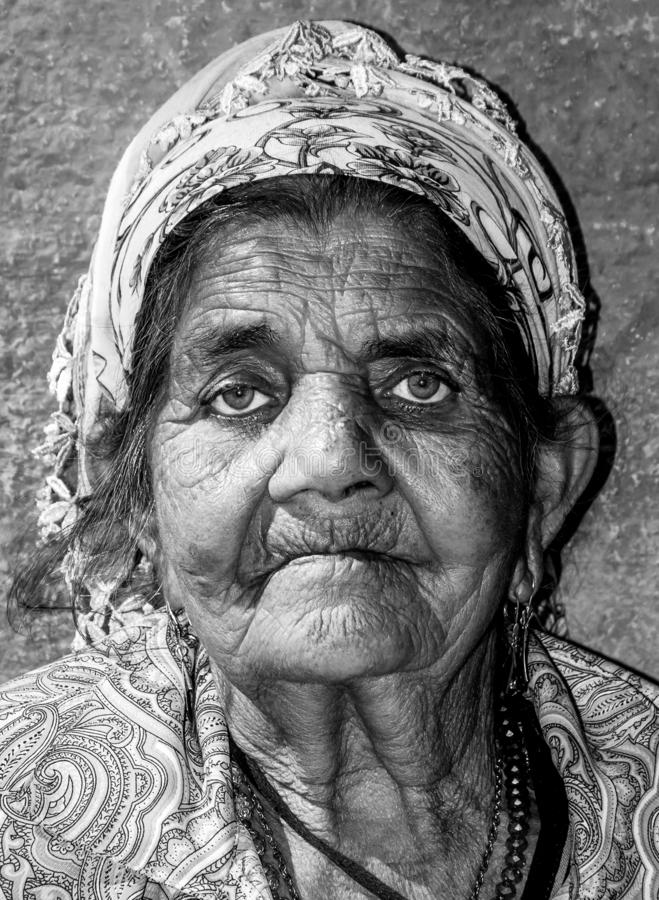 Close up portrait of old homeless Gypsy beggar woman with wrinkled face skin begging for money on the street in the city and looki stock photo