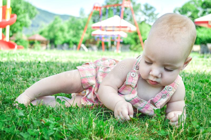 Close up. Portrait of a one year old 9 month old toddler in a pink sundress. She lies on a lush green lawn stock photo