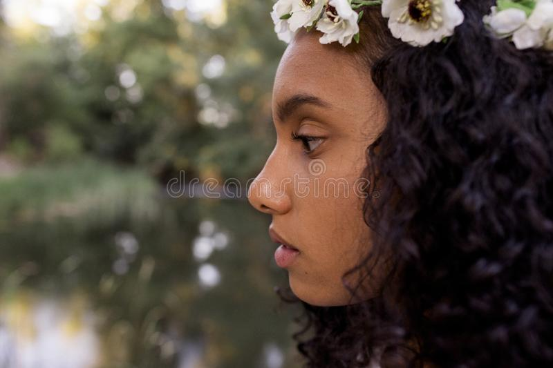Close up portrait outdoors of a beautiful young afro american woman at sunset. Green background. Lifestyle. Wearing white casual stock photos