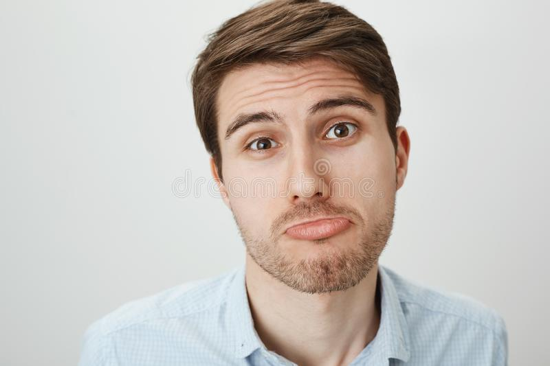 Close-up portrait of pity cute caucasian guy making angel face and sulking, feeling blame and trying to make innocent. Expression, standing over gray background stock photography