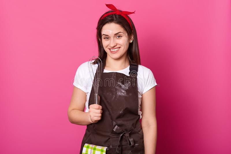 Close up portrait of pleased young housewife finishes making chocolate cake. Attractive girl soiled with flour looks happy, stands stock photos