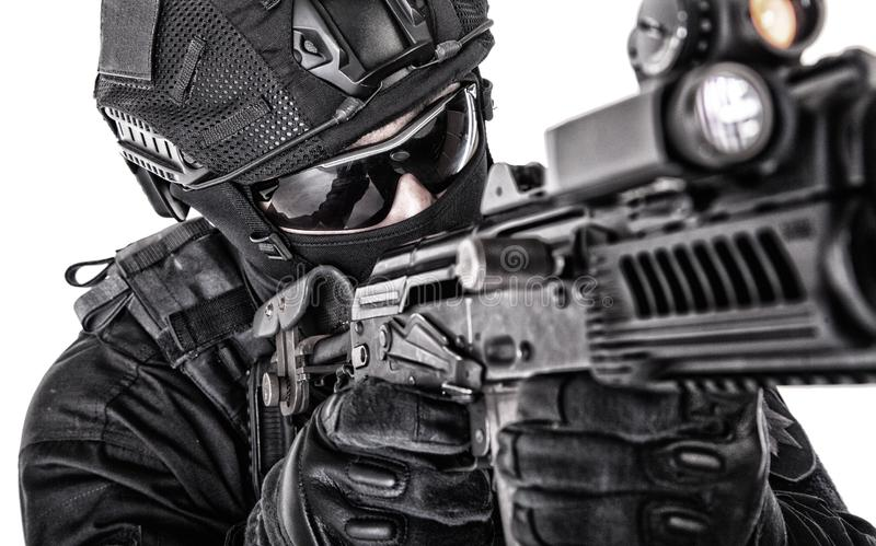 Police special forces fighter closeup studio shoot. Close up portrait of police tactical team fighter, SWAT officer in black uniform, helmet, hidden behind mask royalty free stock images