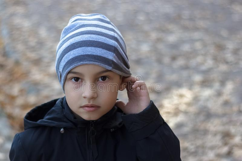 Close-up portrait of a poor child with hearing problems, holding his hand near his ear, showing me that he does not hear stock photos