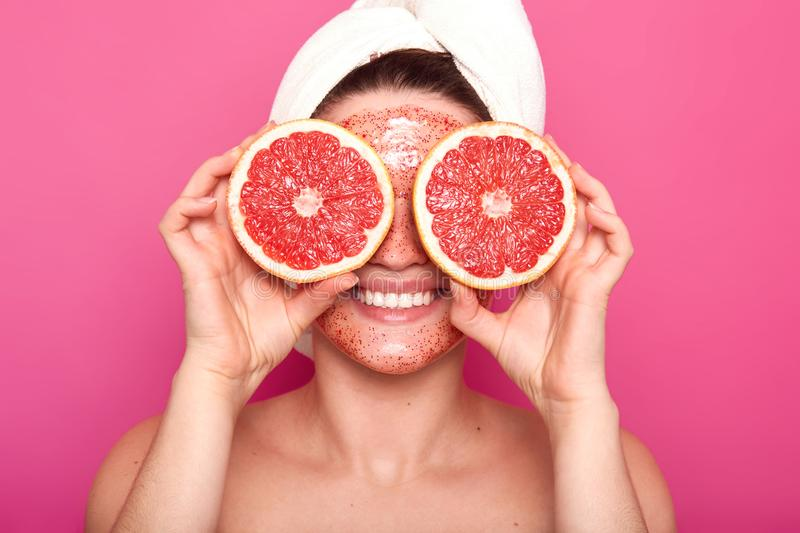 Close up portrait of positive attractive girl smiling sincerely, holding two parts of grapefruit, covering her eyes with fruite, stock photography