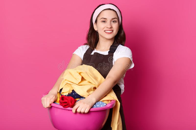 Close up portrait of positive European woman holds basin with clean clothes, has toothy smile, prepares for washing, wears royalty free stock image