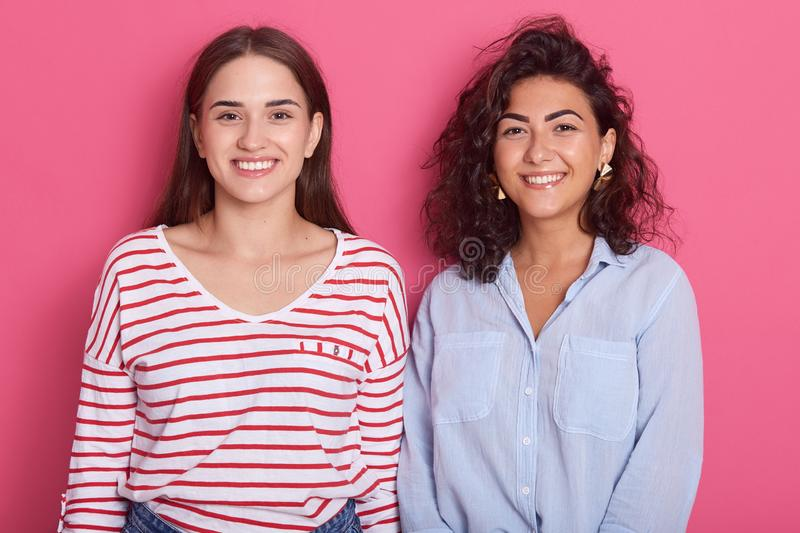Close up portrait of positive ladies standing next to each other, posing with pleasant smiles isolated over rose studio background stock photo