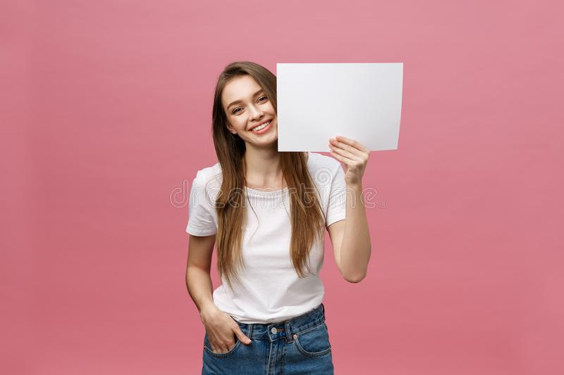 Close up portrait of positive laughing woman smiling and holding white big mockup poster isolated on pink background.  stock photos