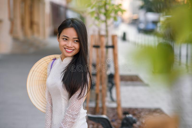 Close up portrait of pretty asian girl dressed in Ao Dai dress with vietnamese conical hat against arches background. royalty free stock photo