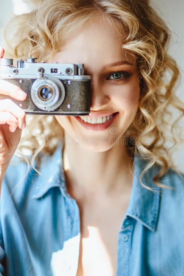 Close up portrait of pretty blonde young woman with old vintage camera in her hands royalty free stock images