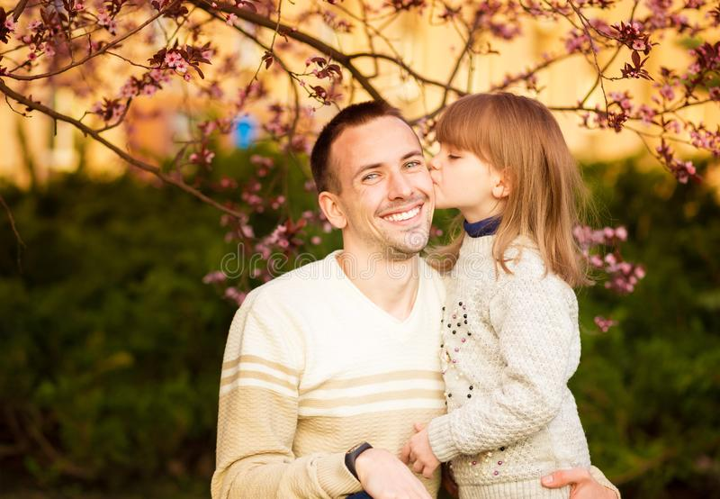 portrait pretty daughter embracing Caucasian father. Family enjoy spend time together. Happy diverse family stock photo