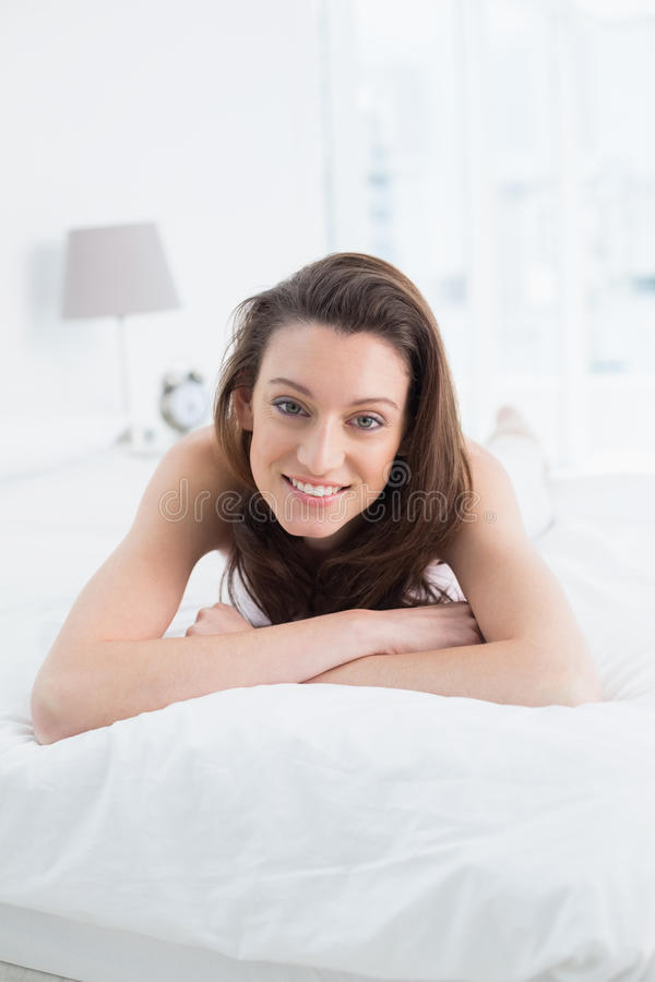 Close up portrait of pretty happy woman resting in bed royalty free stock photography