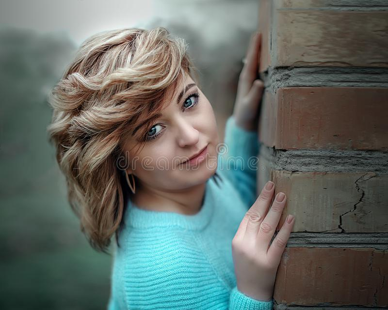 Close-up portrait of a pretty woman standing next to the break wall outside stock images