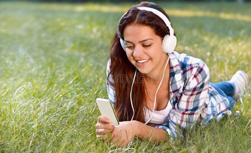 Close up portrait of pretty young girl listening music lying at the grass royalty free stock photos