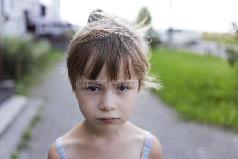 Close-up portrait of pretty young little blond pale unhappy moody friendless child girl looking sadly in camera on blurred sunny o royalty free stock images