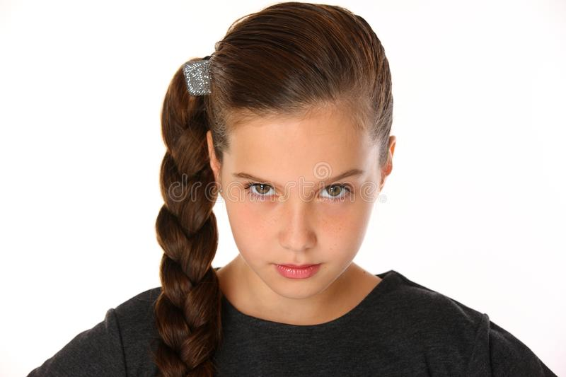 Close-up portrait of pretty young schoolgirl. She is serious and demanding stock photography