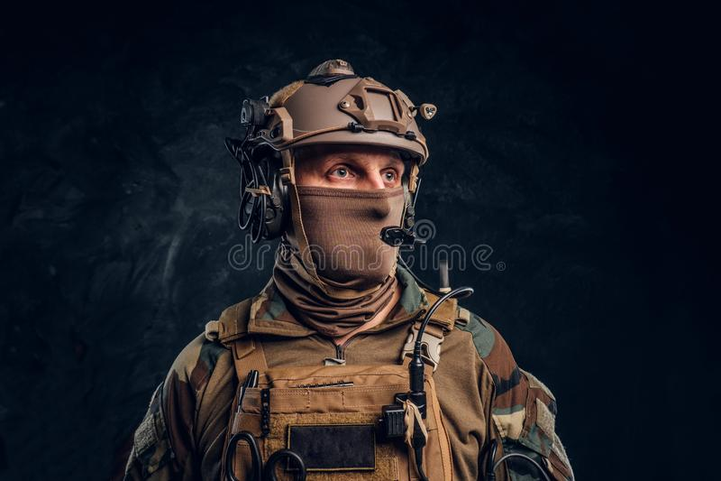 Close-up portrait. Private security service contractor in camouflage helmet with walkie-talkie. stock photos