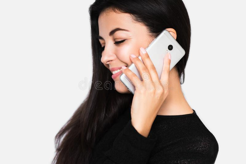 Close up portrait in profile of attractive young happy woman with closed eyes with smart phone with healthy toothy smile royalty free stock photography