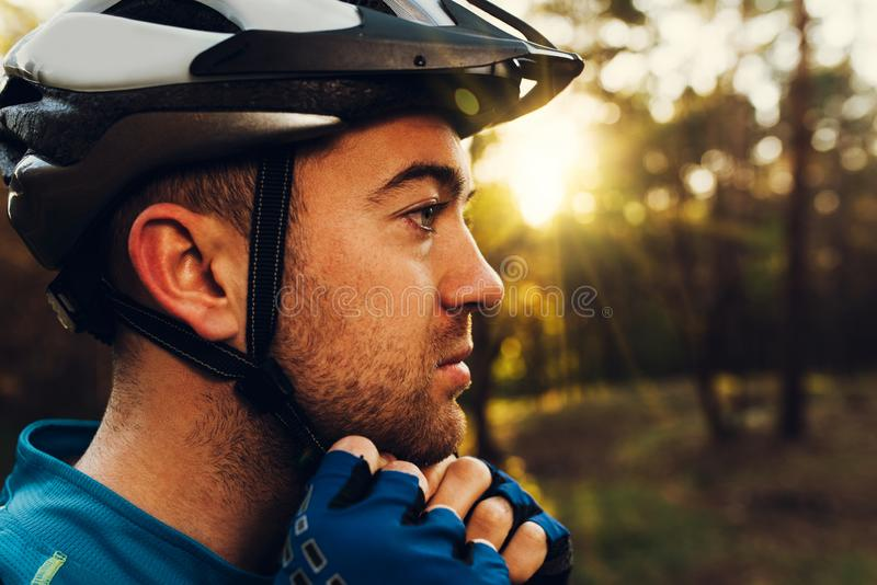 Close up portrait in profile of handsome and serious cyclist close his protective helmet outdoors and looking away, thinking about royalty free stock images