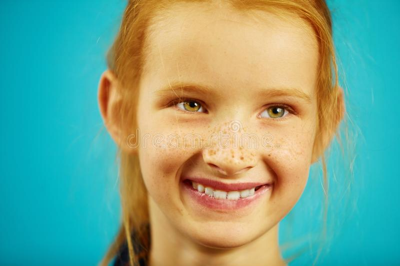 Close-up portrait of red haired girl with freckles, smiles sincerely, has a good mood, expresses sincerity and honesty. On isolated blue background. Concept of stock photography