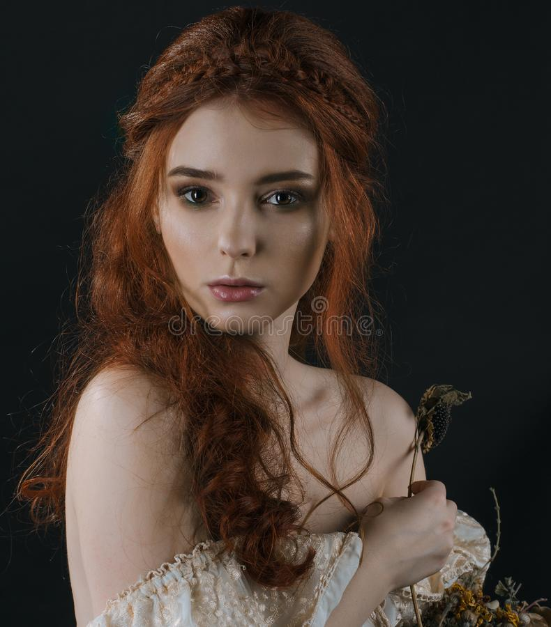 A close-up portrait of a red-haired young woman in a vintage gold dress with bare shoulders with a dry bouquet in hands on a black. Background. A princess stock photo
