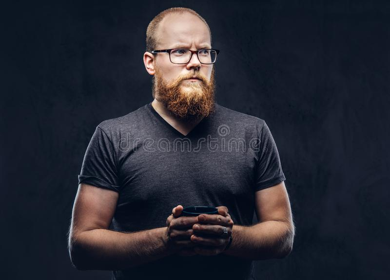 Close up portrait of a redhead bearded male standing with a warming cup of coffee wearing glasses dressed in a gray t. Shirt, isolated over a dark textured stock image