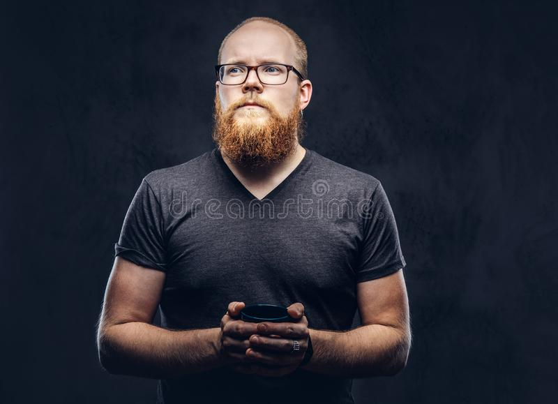 Close up portrait of a redhead bearded male standing with a warming cup of coffee wearing glasses dressed in a gray t. Shirt, isolated over a dark textured stock images