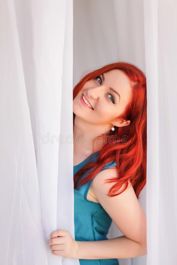 Close up portrait of redhead young happy lady in casual clothes playfully looks out from behind curtain royalty free stock image